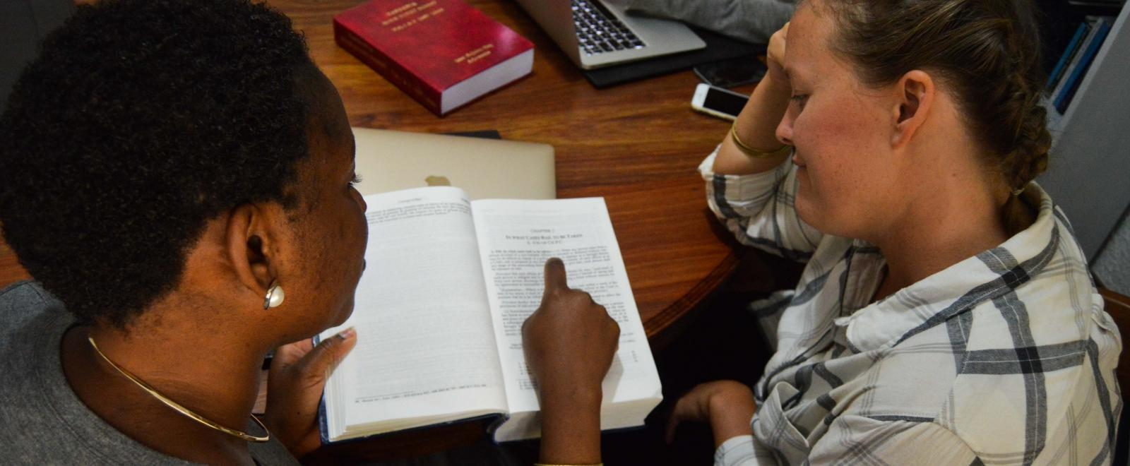 A student is assisted by a Projects Abroad staff member during her Human Rights internship in Tanzania.